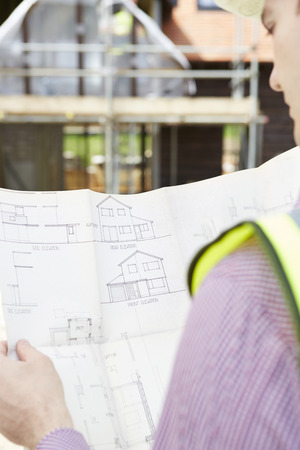 outoors: Architect On Building Site Looking At Plans For House
