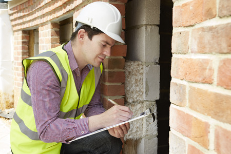 building safety: Architect Checking Insulation During House Construction Stock Photo