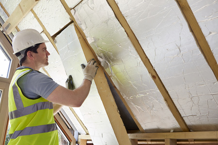 insulating: Builder Fitting Insulation Into Roof Of New Home