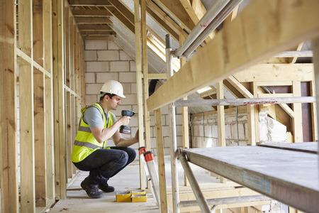 building house: Operaio edile utilizzando trapano Sulla Casa Costruire