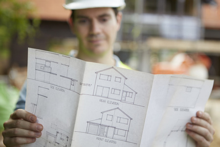 outoors: Construction Worker On Building Site Looking At House Plans Stock Photo