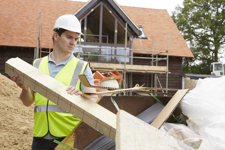 construction site helmet: Builder Putting Waste Into Rubbish Skip Stock Photo