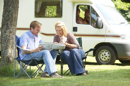 Couple Relaxing Outside Motor Home On Vacation Stock Photo