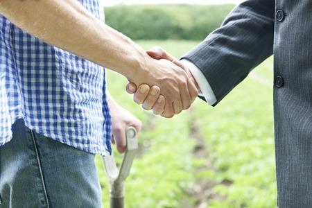 dandose la mano: Agricultor y hombre de negocios que sacuden las manos