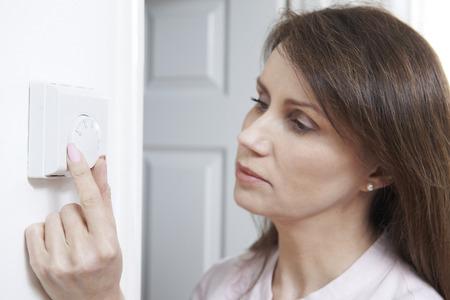 electricity generation: Woman Adjusting Thermostat On Central Heating Control Stock Photo