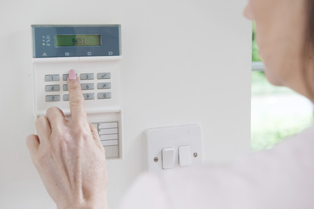alarm system: Woman Setting Control Panel On Home Security System Stock Photo