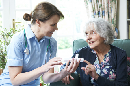 medications: Nurse Advising Senior Woman On Medication At Home
