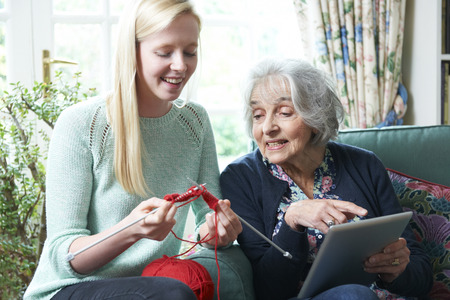 19 years old: Grandmother Using Digital Tablet As Granddaughter Knits Stock Photo