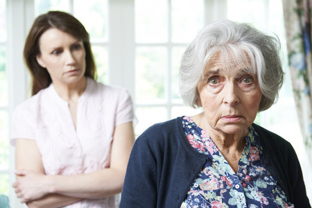 senior female: Serious Senior Woman With Worried Adult Daughter At Home