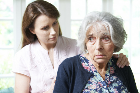 woman serious: Adult Daughter Consoling Senior Mother At Home