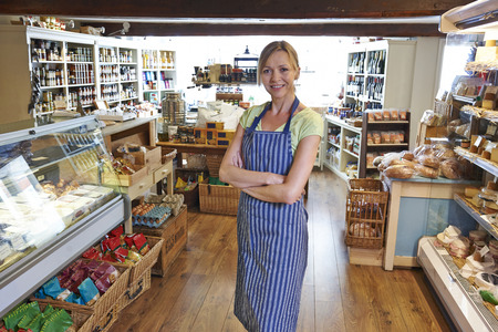 small business owner: Owner Of Delicatessen Standing In Shop