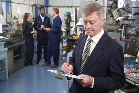 portapapeles: Propietario de la fábrica Ingeniería con el personal en el fondo