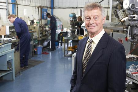 business: Besitzer von Engineering-Fabrik mit Mitarbeitern im Hintergrund