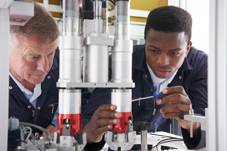 boy 18 year old: Engineer And Apprentice Working On Machine In Factory