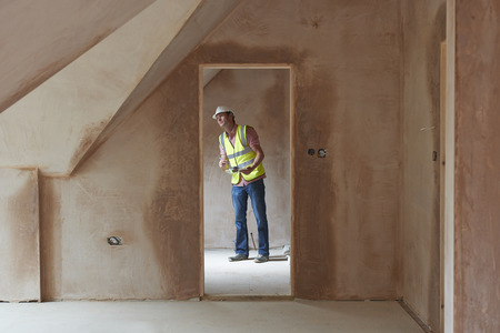 home builder: Building Inspector Looking At New Property Stock Photo