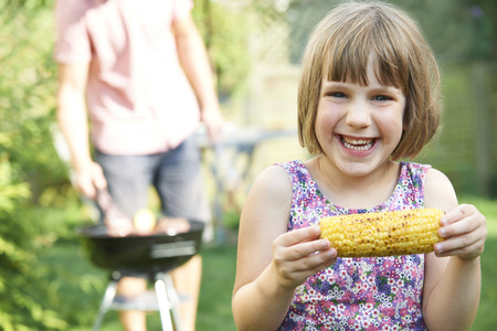 sweetcorn: Young Girl Eating Sweetcorn At Family Barbeque
