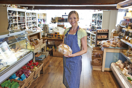 pastry shop: Owner Of Delicatessen Standing In Shop Holding Loaf Of Bread