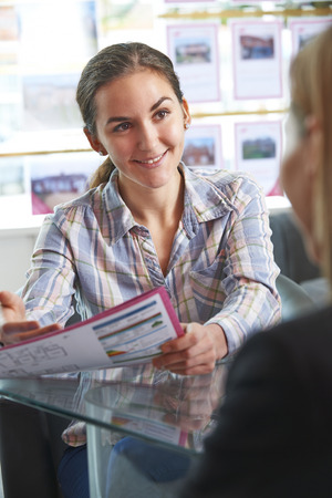 brochures: Estate Agent Discussing Property With Client In Office