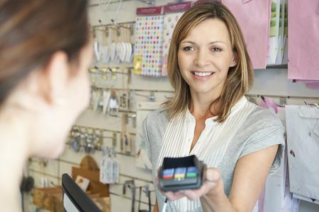 pagando: Comprador paga por bienes que usa la máquina de tarjetas de crédito