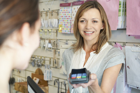 paying with credit card: Shopper Paying For Goods Using Credit Card Machine