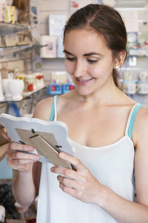Female Shopper Looking At Picture Frame In Gift Shop photo