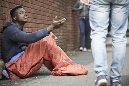 hombre pobre: Adolescente sin hogar pidiendo dinero en la calle Foto de archivo