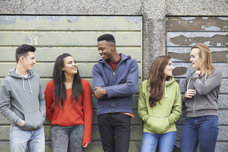 teenagers laughing: Gang Of Teenagers Hanging Out In Urban Environment Stock Photo