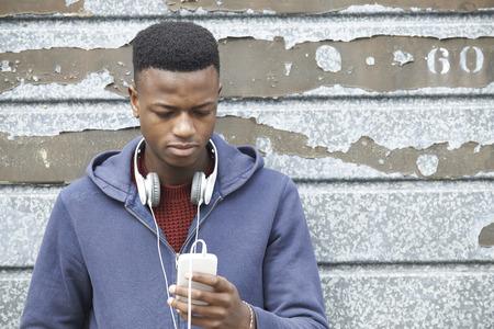 hombre viejo: Adolescente con aud�fonos y escuchar la m�sica en el ambiente urbano Foto de archivo