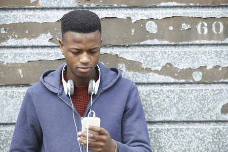 Teenage Boy Wearing Headphones And Listening To Music In Urban Setting