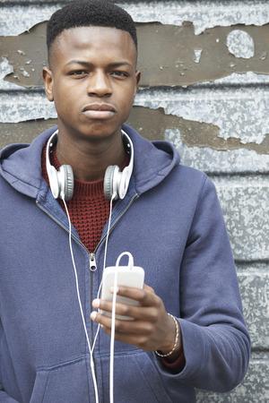boy 18 year old: Teenage Boy Wearing Headphones And Listening To Music In Urban Setting