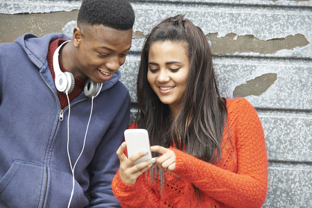 two: Teenager Couple Sharing Text Message On Mobile Phone
