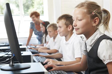uniform: Grupo de alumnos de primaria en clase del ordenador con el profesor Foto de archivo