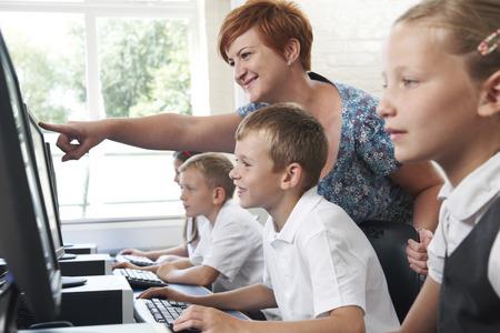 onderwijs: Mannelijke Elementaire Leerling In Computer klasse met Leraar