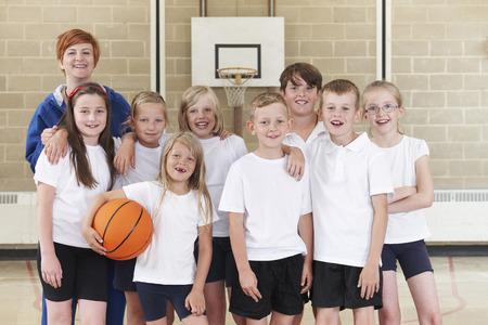educacion fisica: Escuela Primaria Equipo Baloncesto con el entrenador Foto de archivo