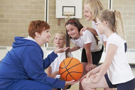 physical education: Teacher Giving Team Talk To School Basketball Team Stock Photo