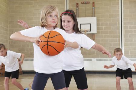 baloncesto chica: Los alumnos de la escuela primaria que juegan a baloncesto en gimnasia Foto de archivo