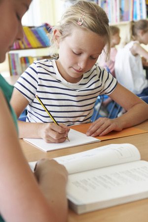 8 years: Elementary School Pupil Working At Desk In Classroom Stock Photo