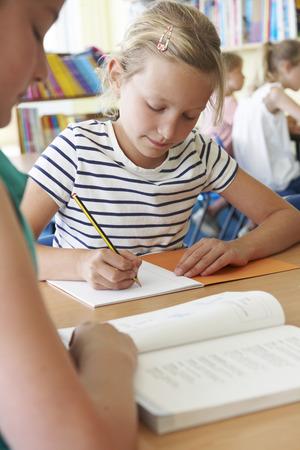 ni�os con l�pices: Escuela Primaria alumno trabaja en el escritorio en sala de clase