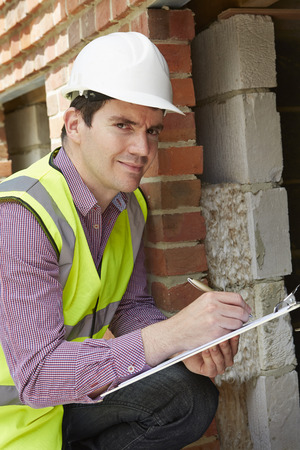 lagging: Architect Checking Insulation During House Construction Stock Photo
