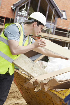 high visibility: Builder Putting Waste Into Rubbish Skip Stock Photo
