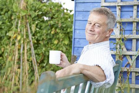 Senior Man ontspannen in de tuin met een kopje koffie