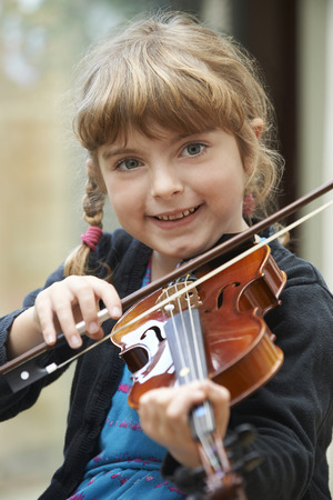 enfant qui joue: Young Girl Learning To Play Violin Banque d'images