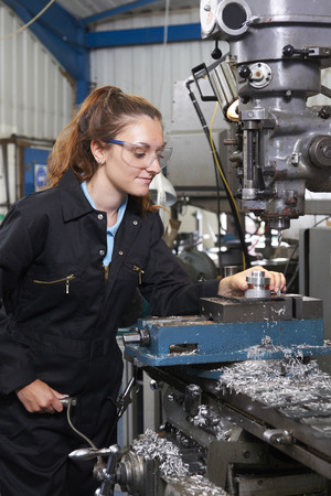 apprentice: Female Apprentice Engineer Working On Drill In Factory Stock Photo