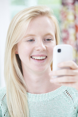 19 years old: Smiling Young Woman Reading Text Message