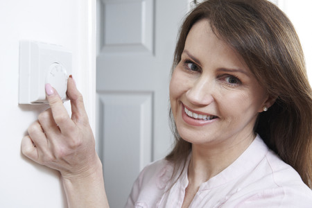 Woman Adjusting Thermostat On Central Heating Control Stock Photo