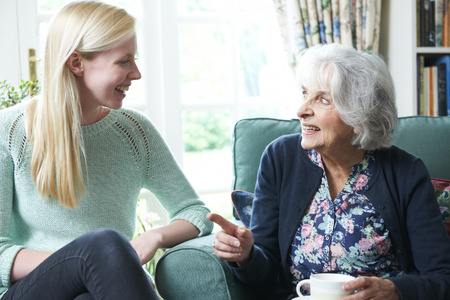 Teenage Granddaughter Visiting Grandmother Stock Photo