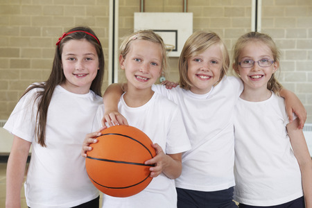 basketball team: Female School Sports Team In Gym With Basketball