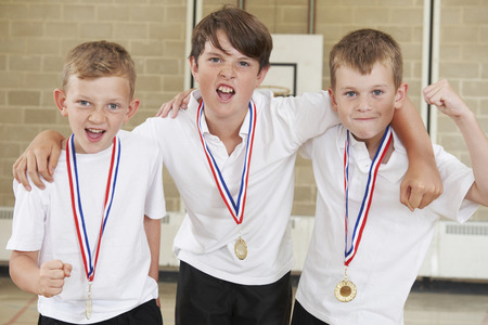 sport team: Male School Sports Team In Gym With Medals