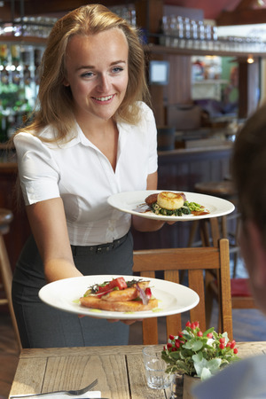 food industry: Waitress Serving Customer Sitting At Table In Restaurant