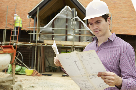 worker construction: Architect On Building Site Looking At House Plans Stock Photo